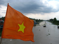 A canal in the Mekong Delta (omnia2070) Tags: red water yellow star boat canal vietnamese rice paddy flag delta an vietnam mekong province giang oceo