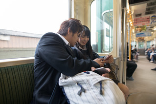 High school student couple commuting on train