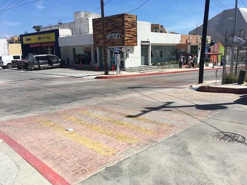 Fading yellow zebra paint over textured crosswalk