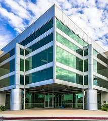 Green Symmetry (PhotonLab) Tags: green symmetry building architecture greenglass day clouds bluesky greenwindows greentint geometric businessbuilding office sony sonya7ii zeiss batis225