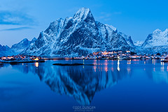 Reflection of Olstind mountain peak in harbour at Reine, Lofoten Islands, Norway (nihad hazeeb) Tags: winter sky mountain snow mountains cold reflection nature water norway landscape outside outdoors lights evening coast landscapes town high scenery european village view streetlights no scenic dramatic peak nobody norwegian coastal coastline fjord watersedge lit scandinavia reine fjords rugged scenics steep arcticcircle fjorden mountainrange lofotenislands northerneurope mountainous mountainpeak beautyinnature olstinden moskenesøy moskenesoy kjerkfjord moskenesøya olstind
