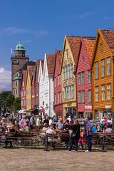 Colorful Bryggen (NykO18) Tags: people building tower art norway shop person woodwork store europe flag business manmade housing bergen bryggen carvings hordaland vestlandet