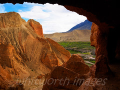 Looking out from the cave (whitworth images) Tags: nepal red green nature beautiful grass contrast rural landscape outdoors asia village scenic rocky dry nobody nopeople scene cliffs erosion oasis pasture fields cave stony mustang geology agriculture himalaya arid eroded cavedwellings restrictedarea geologicalfeature springfed uppermustang annapurnaconservationarea dhakmar skycaves