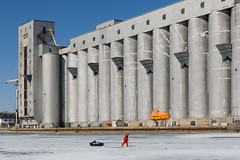 Thin Ice (Bert CR) Tags: grainelevators elevators fisherman icefishing survivalsuit dwarfed ice winter wintersport harbor