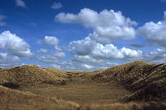dunes and clouds (Ron Layters) Tags: dunes grass clouds nationaalparkzuidkennemerland fence coastland kennermerlandnationalpark bluesky holland noordholland bloemendaal kennemerduinen kenermerland netherlands nederland slidefilmthenscanned slide transparency fujichrome velvia leica r3 leicar3 ronlayters