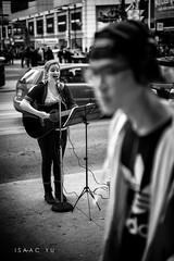 Girl on guitar. Guy on headphones. (IsaacYuPhotography) Tags: street bw musician white playing toronto ontario canada black guy girl monochrome zeiss walking square photography downtown artist singing guitar candid sony isaac center full 55mm frame headphones eaton fe yu alpha dundas a7