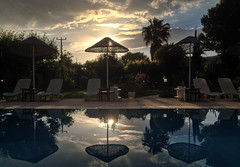 At sunset (VillaRhapsody) Tags: sunset sky sun pool umbrella reflections dusk palm challengeyouwinner swimmignpool