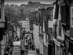 Fore Street, Totnes (Rookie Phil) Tags: historicalbuildings architecture houses shops apartrments victorian tudor gargoyles leadedlights roofaerials chimneys devon totnes bridgetown clocktower churchtower church trees hills vans cars vehicles shoppers pedestrians winter outdoor d750 nikond750 street bw blackwhite monochrome