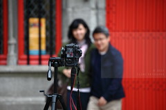A tripod in need is like a friend indeed (Elios.k) Tags: door camera travel red two people woman man west color colour travelling tourism window smile smiling horizontal canon asian outdoors photography photo focus couple alone dof shot belgium bokeh tripod review brugge chinese screen depthoffield westvlaanderen together frame 7d strap april bruges region flemish touristic flanders brgge backgroundblur heiligbloedbasiliek basilicaoftheholyblood 5dmkii focusinforeground