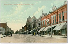 Main Street looking west, Greenfield, Indiana (Hoosier Recollections) Tags: horses people usa signs man color men history buildings awning clothing indiana streetscene bicycles transportation drugs shops pedestrians storefronts greenfield buggy buggies businesses hancockcounty hoosierrecollections vonepageqffalse