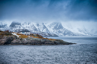 Travel and Tourism Concepts. One Separate House on Seashore Coastline in Norway Against Snowy Mountains.