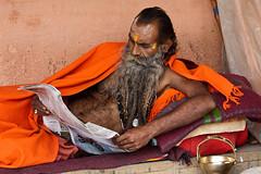 Reading Sadhu (Dick Verton ( more than 13.000.000 visitors )) Tags: travel orange india reading newspaper asia varanasi sadhu ghats laying