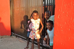 The Devilish, The Sweet and the Bored (...and the Hidden) (Haomin/) Tags: poverty girls sunset red portrait orange sun look smiling pose children southafrica eyes candid 4 group streetphotography roadtrip johannesburg soweto bicycletour amateurmodel olympusepl2