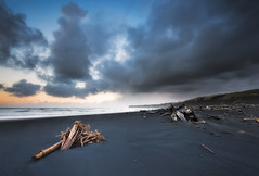 The Battered Coast (Nick Twyford) Tags: longexposure newzealand seascape weather clouds sunrise blacksand waves wideangle driftwood nz northisland westcoast wanganui taranaki earlymorninglight colourimage patea leefilters distantrain nikond800 stormymood manabay lee09nd lee06gndsoft phottixgeoone nikkor160350mmf40