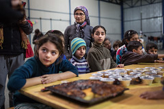 waiting for cake (dominic_wenger) Tags: greece sindos thessaloniki athen frakapor refugee refugees refugeecamp camp military crysis borders open world problem swisscross volunter help portrait face family poor man woman kids chil child children beautiful beauty war syria tent tents hall light dark cold candid looking people human humanity sun boring life flee volunteer frame sigma35 sigma canon 5dmk3 lowlight sigmaart humanism bake cake waiting childrens boy boys girls girl hat eye eat