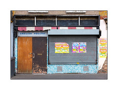 Closed for Business, East London, England. (Joseph O'Malley64) Tags: closedforbusiness defuct laidtowaste butchersshop formerbutchersshop eastlondon eastend london england uk britain british greatbritain shop shopfront vacant empty shutter rollershutter awning billposters thecircusiscomingtotown englishpoultry sign signage doors doubledoors doorway entrance exit locked secured vents mosaictiling tilesonaroll render blownrendering brickwork bricksmortar cement pointing blockpaving wheeliebin drainpipe pebbledashing windowsills culturalchange marketforces patina decay decline urban urbanlandscape fujix accuracyprecision