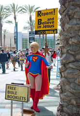 Supergirl surrounded by bible signage (Sonia.Harris) Tags: california comics cosplay religion signage comicbooks bible christianity anaheim wondercon 2014