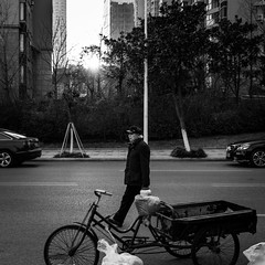 Walking on the street (Go-tea 郭天) Tags: man old walk walking movement back through road pedestrian evening cold winter cap coat bags car trees building qingdao huangdao pot bottle carried carry carrying street urban city outside outdoor people bw bnw black white blackwhite blackandwhite monochrome asia asian china chinese shandong canon eos 100d 24mm prime
