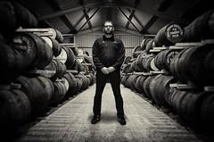 Wolf burn Shane Monochrome Full Length in Warehouse (SubSeaSniper) Tags: wolfburn whisky distillery editorial monochrom portrait moody silverefex2 aperture ricoh compact ricohgr blackandwhite warehouse barrels