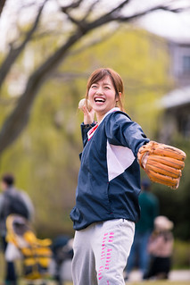 Happy young woman throwing ball to her boyfriend