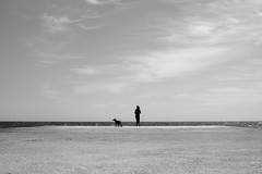 Down on the Jetty, Barcelona (Geraint Rowland Photography) Tags: blancoynegro blackandwhite artisticphotography wwwgeraintrowlandcouk beach water ocean sunshine woman streetphotography candidportrait minimalism sky clouds dog dogwalker geraintrowlandbarcelona barcelona catalonia spain europe