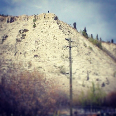 A man hikes along the ridge of clay cliffs, which were cut over years by the #Yukon River #yxy
