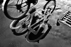 Berlin - street (luca marella) Tags: street blackandwhite bw white black reflection water rain bike bicycle mirror blackwhite reflex pb bn roadsign bianco nero bicicletta twowheeler marellaluca