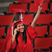 A jubilant grad waves to her family in the PNC Arena audience during spring 2014 commencement.