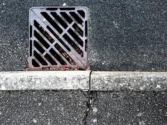 drain grating (friendlydrag0n) Tags: drain grating pavement sidewalk asphalt iron kerb grey gray crack simple minimal