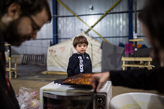 Rohan waiting for cake (dominic_wenger) Tags: greece sindos thessaloniki athen frakapor refugee refugees refugeecamp camp military crysis borders open world problem swisscross volunter help portrait face family poor man woman kids chil child children beautiful beauty war syria tent tents hall light dark cold candid looking people human humanity sun boring life flee volunteer frame sigma35 sigma canon 5dmk3 lowlight sigmaart humanism cake bake wait waiting young boy boys happy cute shy smile laugh unconfertable