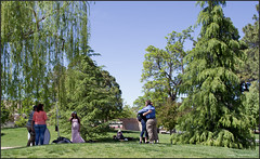 Photographing the photographer (newmexico51) Tags: photographer model hugging man woman trees unm duckpond universityofnewmexico albuquerque nm newmexico gregorypeterson camera stand grass route66
