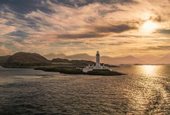 Lismore Lighthouse Sunrise (Bathsheba 1) Tags: uk morning light sea sky panorama sun sunlight seascape mountains reflection building nature water weather architecture clouds sunrise reflections landscape geotagged dawn scotland highland