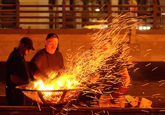 Stoking the Fire (Photograph by John Nickerson) (waterfireprov) Tags: brazier volunteers woodboat
