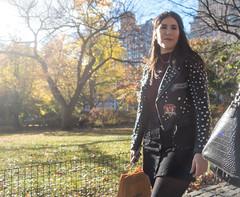 Woman in Central Park (UrbanphotoZ) Tags: woman centralpark leatherjacket studs bluenails inspire diamond lawn trees fence apartmentbuildings smartphone upperwestside manhattan newyorkcity newyork nyc ny