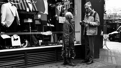 The long and the short of it. (Neil. Moralee) Tags: londonneilmoralee man woman couple street elderly old mature bald black white mono monochrome blackandwhite bandw bw shop clothes london england uk chemo chemotherapy cancer hair loss brave candid people neil moralee nikon d7100 18300mm zoom talking book map lost tourists standing waiting