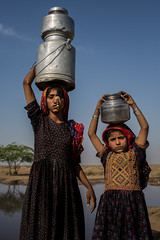 Dhaneta Jat tribe girls carrying water containers on the head in great rann of kutch (anthony pappone photography) Tags: travel girls india water colors silver colours handmade muslim earring piercing ring well rings tribes asie nosering cloth ethnic indi indien nomads indi yat islamic gujarat inde ethnology azi nomadic indland noserings kutch bhuj  jat etnic greatrannofkutch indija  etnia handembroidered ethnie carryingwater collectwater womancarrying dhanetajat dhaneta   jattpeople jatttribe earringnose earringjatjat jattribe desertkutch kutchtribes anthropologye dhanetajattribe