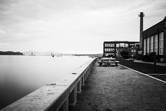 Down by the river (lukasnorth) Tags: bridge chimney sky blackandwhite bw water landscape photography blackwhite factory quiet peaceful serenity serene emotional parkbench benches brickbuilding parkbenches hundsonriver