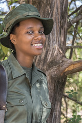Portrait of a woman game ranger (tmeallen) Tags: gameranger woman rifle smiling female khaki posingin shade largetree hat arushanationalpark tanzania eastafrica travel culture
