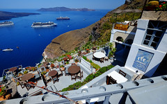 Santorini View of the Caldera in Greece (` Toshio ') Tags: toshio santorini oia fira island caldera greece southernaegeansea sea aegean cruiseships europe european europeanunion architecture city cliff fujixe2 xe2 restaurant cafe tables view ship boat