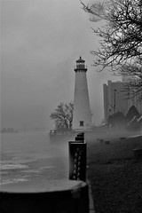HFF-with chain link and lighthouse (SCOTTS WORLD) Tags: adventure architecture america angle detroit digital downtown december detail 313 exploring exhibit water winter trees icy michigan motown midwest motorcity afternoon city cold rainy sky clouds stormy fun fence fog flag lighthouse landscape riverfront river detroitriver ambassadorbridge americana urban usa unitedstates urbanexploring panasonic pov perspective monochrome blackandwhite atmosphere park williamgmilliken 2016 renaissancecenter gm