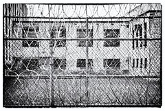 the other side of the fence (ammozug) Tags: bw monochrome fence grass metal razor architecture window bars mens prison closed abandoned