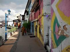 the riverside walk (SM Tham) Tags: asia southeastasia malaysia malacca melaka malaccariver riverside promenade deck walkway buildings walls murals streetart streetlamps pots plants people water boat