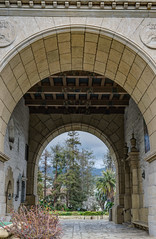 Under the Arch (tquist24) Tags: california hdr nikon nikond5300 santabarbara santabarbaracountycourthouse santaynezmountains arch arches architecture clouds courthouse geotagged mountains sky tree trees vacation unitedstates