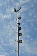 Trading the limelight for floodlights (Jake (Studio 9265)) Tags: mill race park columbus indiana in usa united states america stage lighting auditorium outdoors pole metal march 2017 nikon d5000 lights spotlight flood light floodlight sky blue clouds gray silver