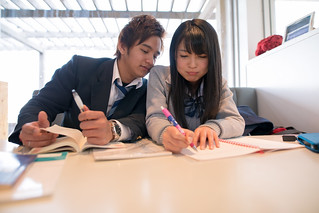 High school students studying together after lunch at cafe
