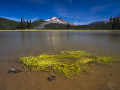 Sparks Lake Shallows (RobertCross1 (off and on)) Tags: 1250mmf3563mzuiko bend cascaderange cascades deschutes deschutesnationalforest em5 omd or olympus oregon pacificnorthwest southsister sparkslake threesisters bluesky forest grass lake landscape mountains nature sand snow trees volcano water