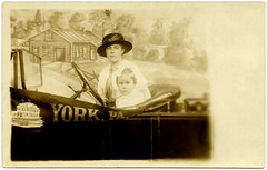 Mother and Daughter Motorists, York, Pa. (Alan Mays) Tags: york old flowers girls cars portraits vintage buildings children souvenirs clothing women funny humorous photos pennsylvania antique humor hats daughters ephemera mothers clothes pa photographs postcards autos amusing bows automobiles drivers windshields foundphotos backdrops steeringwheels yorkcounty hairbows motorists rppc souvenirphotos realphotopostcards studioprops photographicamusements
