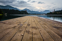 Lake Bled, Slovenia (eva urban) Tags: wood blue summer lake mountains church water clouds forest pier peace smooth pebble slovenia bled