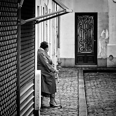 expectations (White_V) Tags: street door old city woman house paris shop standing canon waiting path streetphotography wb elderly stick 2014 whiteandblack bildings