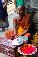 Blessings (Five Second Rule) Tags: cambodia 2017 siemreap temples angkorwat architecture ruin history culture building structure ancient monk blessings religion buddhism orange man robes ceremony donations bracelet prayer people